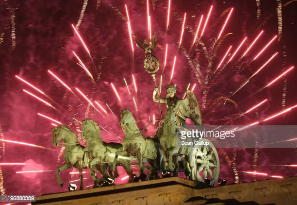 The Quadriga statue stands on the Brandenburg Gate during New Year's Eve fireworks on January 01 2020 in Berlin Germany Germany is ushering in the...