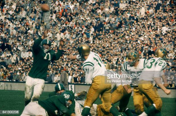 The quaterback of the Notre Dame Fighting Irish throws a pass over a Michigan State Spartans defender during their game on October 17 1959 at Spartan...