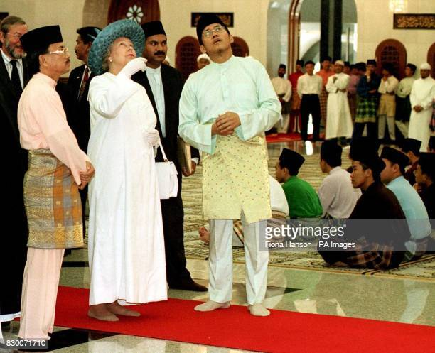 The Queen dressed in a Muslim 'gamis' made especially for her and brought from England admires the ceiling of the male prayer room while touring the...