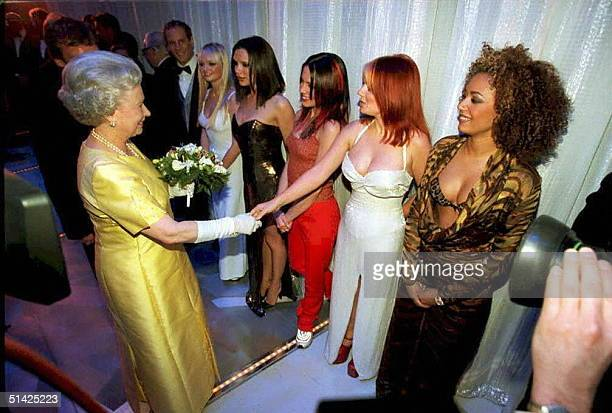 The Queen Elisabeth II shakes hands with Geri Halliwell of the pop group 'Spice Girls' as Emma Victoria Mel C and Mel B look on after 01 December...