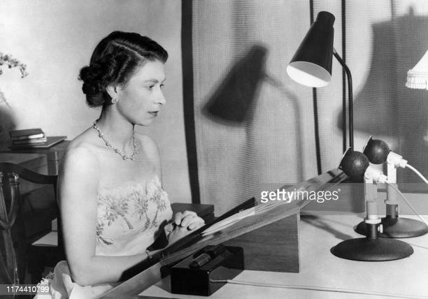 The Queen Elizabeth II, wearing a strapless evening gown, makes her Christmas broadcoast to the peoples of the British Commonwealth, 31 December 1953...