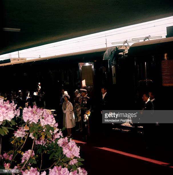 The Queen Elizabeth just got off the train and stands on the platform of the Roma Ostiense railway station beside of her husband Prince Philip...