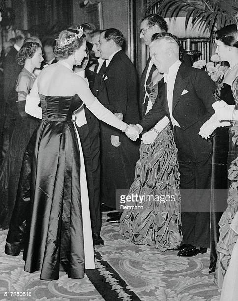 The Queen Greets Chaplin. London, England: England's Queen Elizabeth II greets famed comedian Charlie Chaplin, who is accompanied by his wife, the...