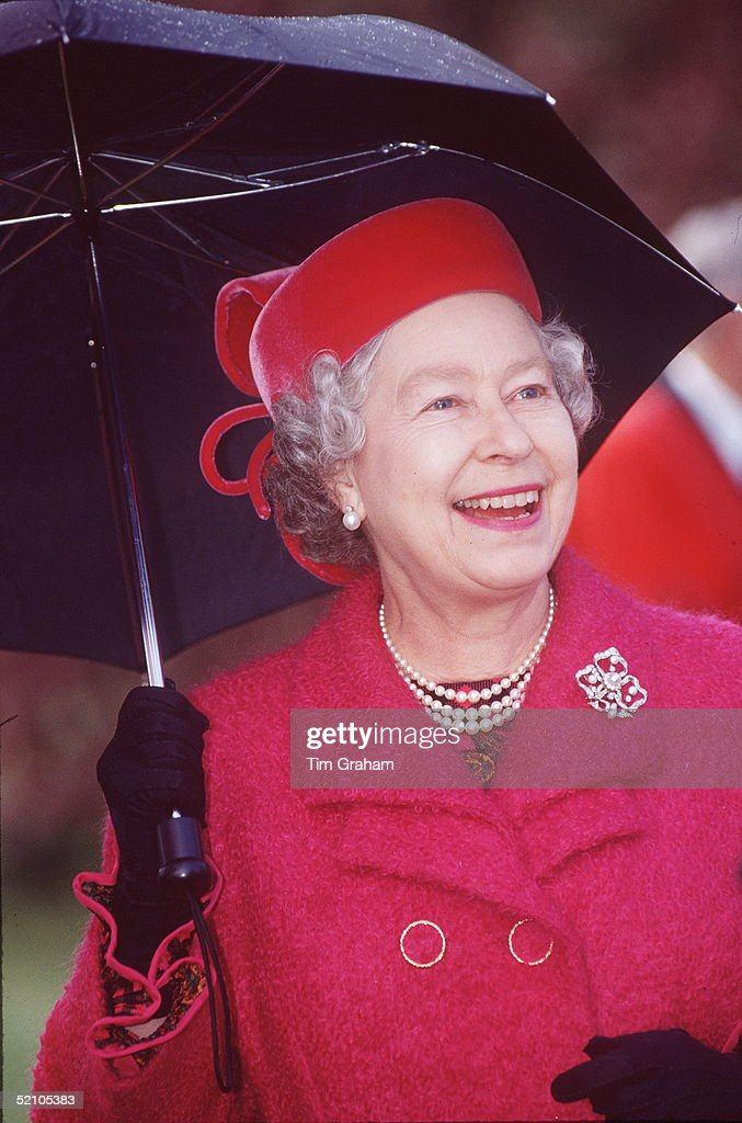 The Queen Holding An Umbrella In The Rain At Emmanuel College, Cambridge.