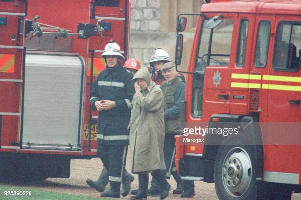 The Queen is escorted by the chief fire officer around the grounds of Windsor Castle as firefighter battle the fire in the Brunswick Tower of the...