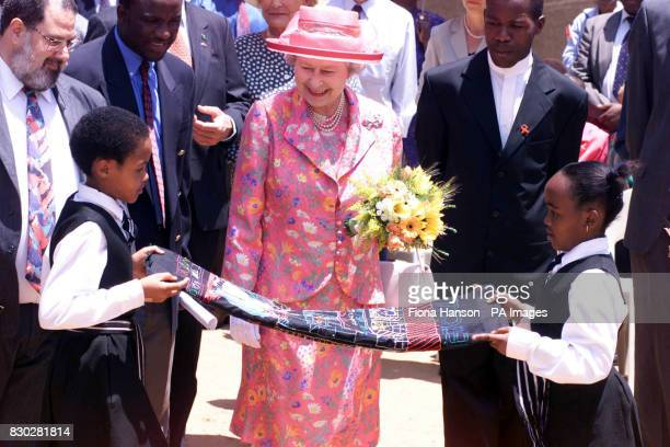 The Queen is presented with an embroidery by children at the Alexandra Adult Education Centre Alexandra Township near Johannesburg South Africa In a...