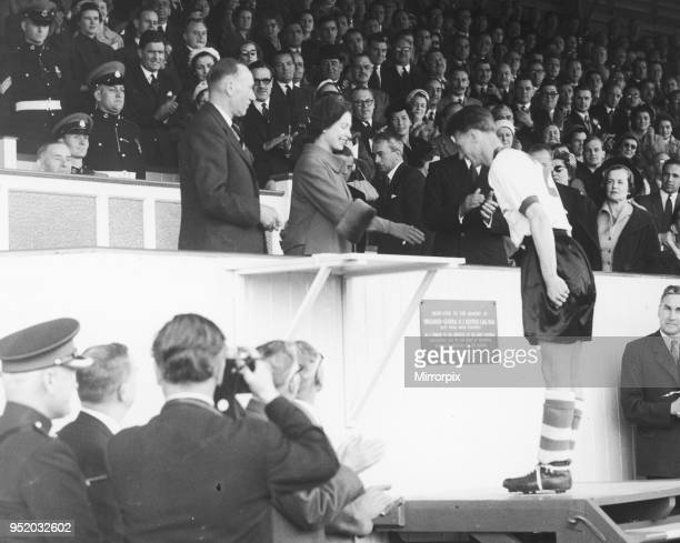The Queen is seen here presenting medals to a member of the R.A.P.C. The losing side in the Army Association Football Cup Final at Aldershot. The...