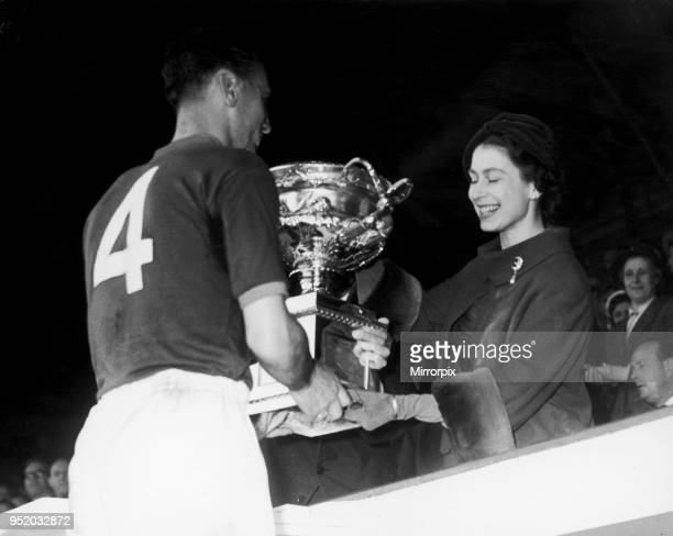 The Queen is seen here presenting the cup to Craftsman R. Nelson, Captain of the R.E.M.E team, who won one nil in the Army Association Football Cup...