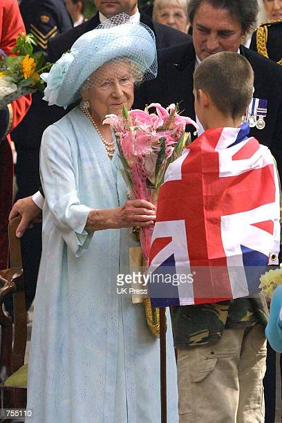The Queen Mother accepts a bouquet of flowers from a young admirer outside Clarence House on the occassion of her 101st birthday celebration August 4...