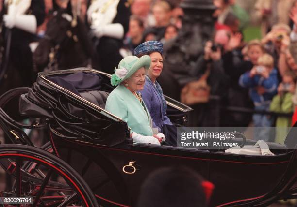The Queen Mother and Princess Margaret smile at the crowds inspite of the wet weather as they make their way in an open carriage down the Mall in the...
