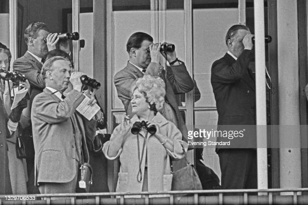 The Queen Mother attends the Grand National at Aintree, accompanied by racehorse trainer Peter Cazalet , UK, 27th March 1965.