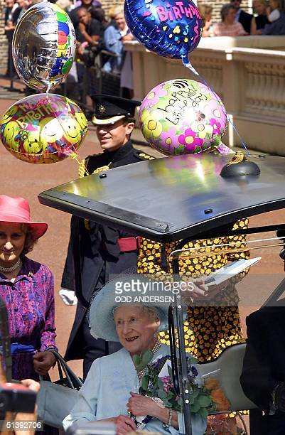 The Queen Mother greets the crowd from her buggy on her 101st birthday at Clarence House in London 04 August 2001 Hundreds of people have been...