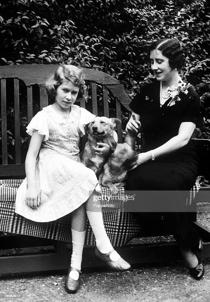 The Queen Mother pictured as The Duchess of York with her daughter Princess Elizabeth (later Queen Elizabeth II), who holds a pet dog, in the garden of their home, 1936. : News Photo