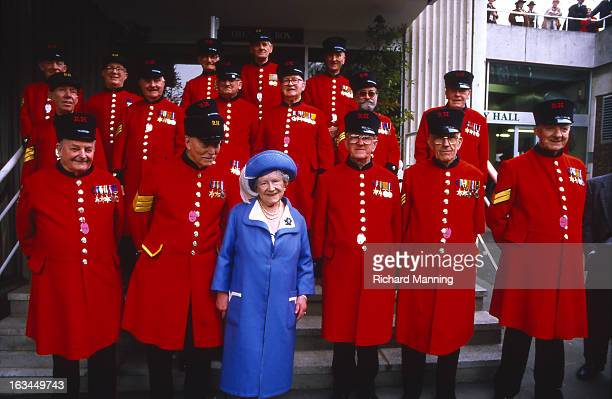 The Queen Mother poses with Chelsea Pensioners whilst attending the Grand Military Gold Cup held annually at Sandown Park Racecourse in Esher Surrey...