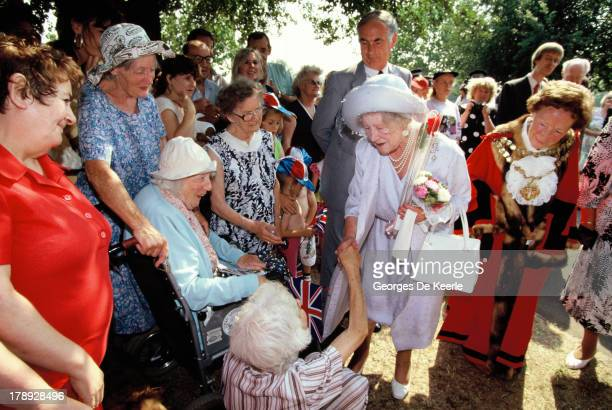 The Queen Mother shakes hands with an old lady during her visit to The East End on August 1 1990 in London England