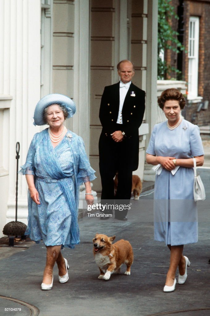 The Queen Mother, Smiling, With Her Daughter, Queen Elizabeth Ll, Outside Clarence House With Her Pet Corgi On Her 83rd Birthday. The Queen Mother Is Wearing A Blue Patterned Chiffon Dress And Blue Hat.