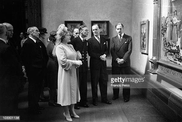 The Queen Mother views a painting as King George VI talks to British art historian Sir Kenneth Clark at the National Gallery London where they were...