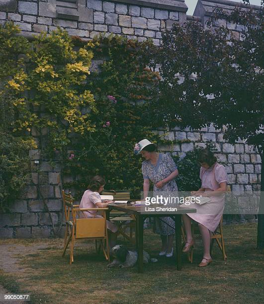 The Queen Mother watches over Princess Margaret and Princess Elizabeth reading in the grounds of Windsor Castle in England on 8 July 1941.