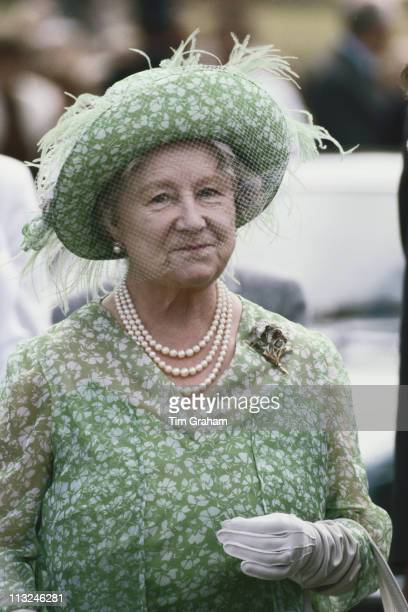 The Queen Mother wearing a green and white floral print dress with a matching hat decorated wi|th pale green feathers and a net veil attending the...