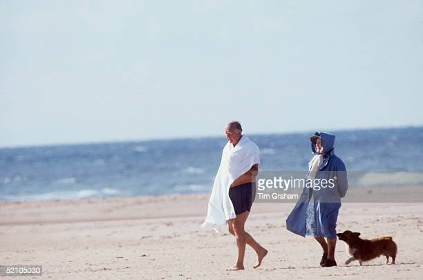 The Queen Mother With A Friend Walking Along The Beach With Her Pet Corgi It Is A Windy Day So The Queen Mother Has Covered Her Hat With The Hood Of...