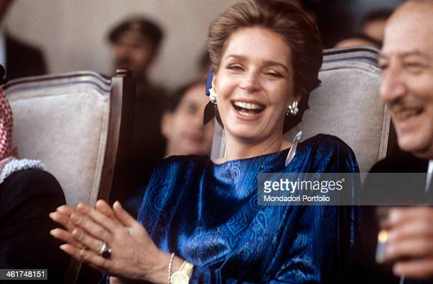 The Queen Noor of Jordania very elegant in her blue dress attends enthusiastically a show staged at a public event at her side on the grandstand...