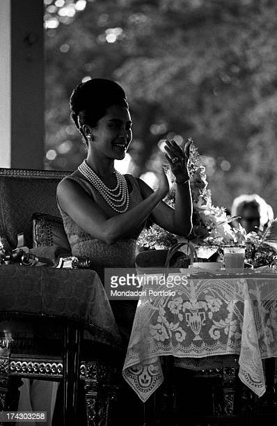 The Queen of Thailand Sirikit sitting at a table and reading during a fashion show Bangkok 1965