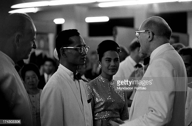 The Queen of Thailand Sirikit waving her fan during a fashion show Bangkok 1965