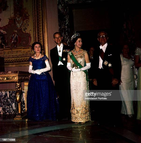 The Queen of the United Kngdom in a sequins tulle dress stands in a hall of the Quirinal Palace between the italian President of the Republic...