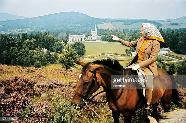 The Queen on horseback looking towards Balmoral Castle, Scotland in the distance during the Royal Family's annual summer holiday in September 1971....