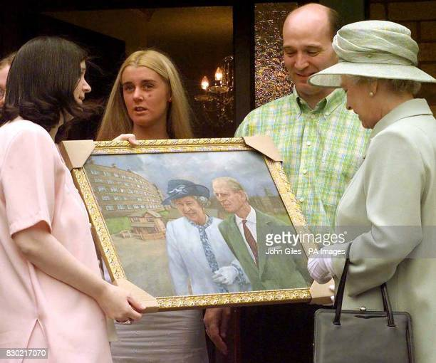 The Queen receives a painting of her visit with the Duke of Edinburgh to St Andrews Gardens Estate in Liverpool presented by Brenda Prendergast and...