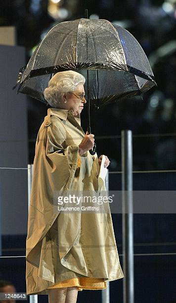 The Queen shelters from the torrential rain under an umbrella during her speech at the Closing Ceremony of the 2002 Commonwealth Games at the City of...