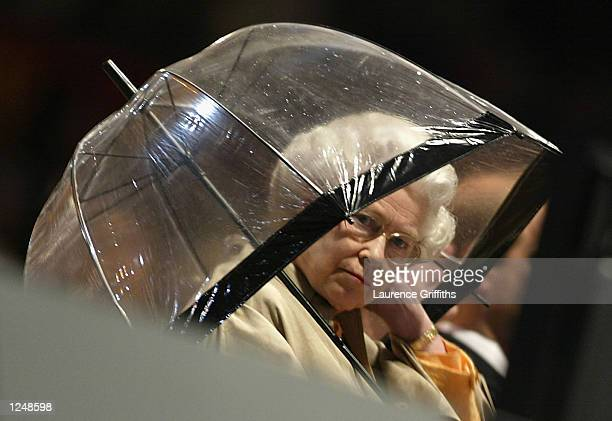 The Queen shelters under an unbrella from the torrential rain during the Closing Ceremony of the 2002 Commonwealth Games at the City of Manchester...