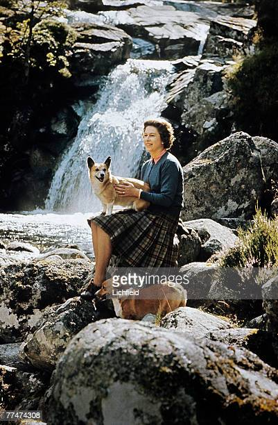 HM The Queen sitting on rocks beside a waterfall on the Garbh Allt burn with two corgis on the Estate at Balmoral Castle Scotland during the Royal...