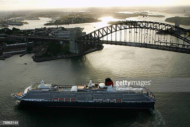 The Queen Victoria Ship reverses in front of the SYdney Harbour Bridge as it approaches the fellow Cunard luxury liner the Queen Elizabeth II ship at...