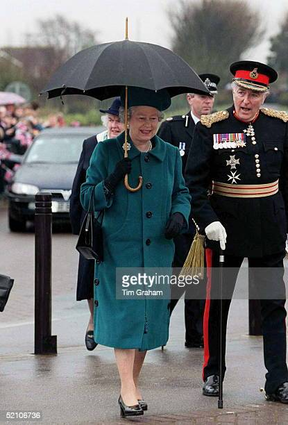 The Queen walks with the Lord Lieutenant during A Visit To Durrington High School In Worthing West Sussex In The Rain