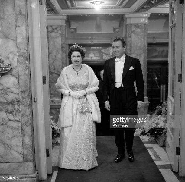 The Queen wearing a shimmering frock of blue and white taffeta glistening with diamante and a white fur wrap is escorted by Mr Bernard Delfont in to...