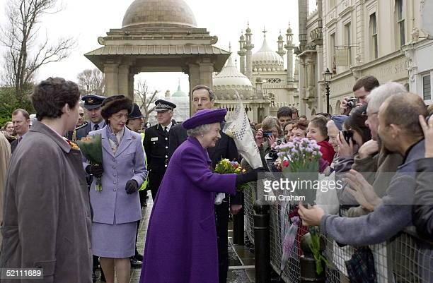 The Queen [ With Bodyguard Chief Inspector Richard Griffin Behind Her And Her Ladyinwaiting Lady Susan Hussey Beside Her ] Being Given Flowers By...