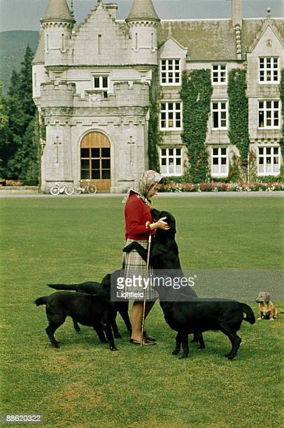 HM The Queen with her dogs on the lawn in front of Balmoral Castle Scotland during the Royal Family's annual summer holiday in September 1971 Part of...