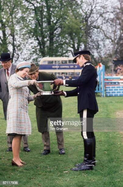 The Queen With Prince Philip And Mark Phillips Their Soninlaw Holding The Winner's Trophy At Crookham Horse Trials In The 1970s