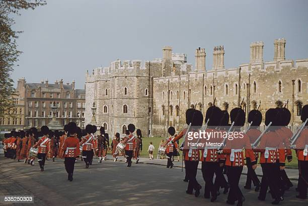 The Queen's Guard marching on Thames Street at the front of Windsor Castle, Berkshire, England, circa 1960.