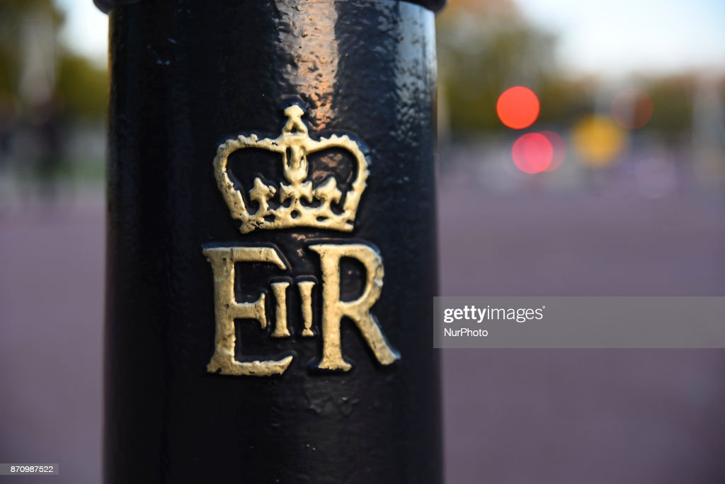 The Queen's monogram is seen against the backdrop of Buckingham Palace as the sun sets, London on November 6, 2017. About £10m of the Queen's private money was invested offshore, leaked documents show. The Duchy of Lancaster, which provides the Queen with an income, held funds in the Cayman Islands and Bermuda.