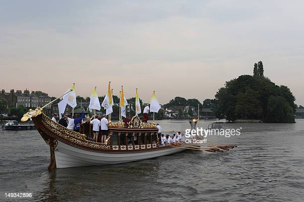 The Queen's rowbarge 'Gloriana' carries the Olympic flame along the river Thames from Hampton Court to City Hall on the final day of the London 2012...