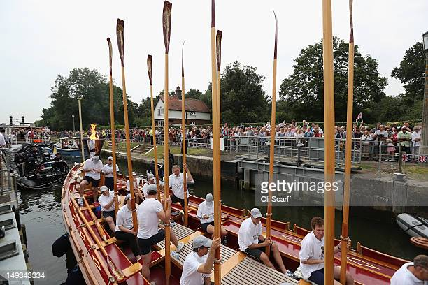 The Queen's rowbarge 'Gloriana' negotiates Teddington Lock as she carries the Olympic flame along the river Thames from Hampton Court to City Hall on...