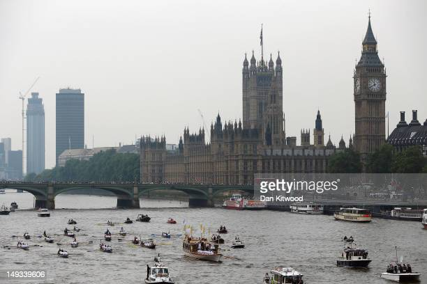 The Queen's royal rowbarge Gloriana carries the Olympic flame along the river Thames past the Houses of Parliament on the final day of the London...