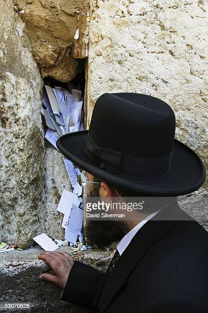 The Rabbi of the Western Wall Rabbi Shmuel Rabinovitch recites a prayer after placing letters to God between the ancient stones of Judaism's holiest...