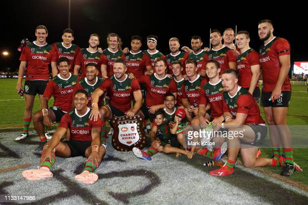 The Rabbitohs team pose with the Charity Shield after victory in the NRL Trial match, which is the Charity Shield match between the South Sydney...