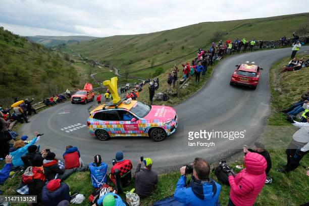 The race caravan climbs the Cote de Park Rash ascent near the village of Kettlewell in the Yorkshire Dales ahead of the arrival of the peloton during...