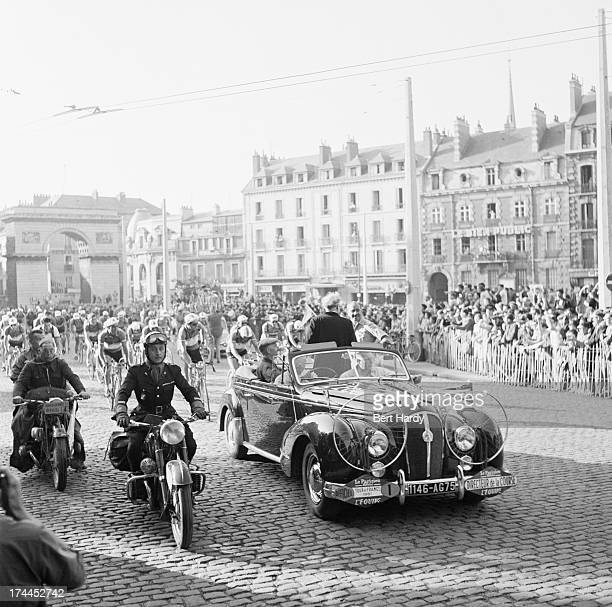 The race director's car leads the riders out of a town square on a stage in the Tour de France August 1951 Original publication Picture Post 5381 The...