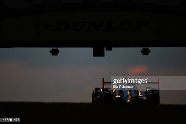 The race winning Porsche Team 919 Hybrid of Earl Bamber, Nick Tandy and Nico Hulkenburg drives under the Dunlop Bridge at dawn during the Le Mans 24...