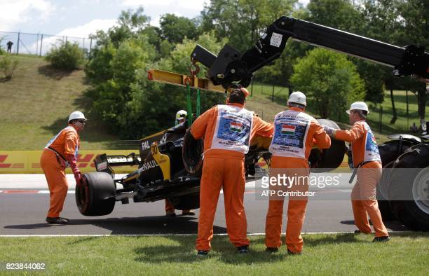 The racing car of Renault's British driver Jolyon Palmer is lifted off the racetrack after a tyre blowout during a practice session at the...